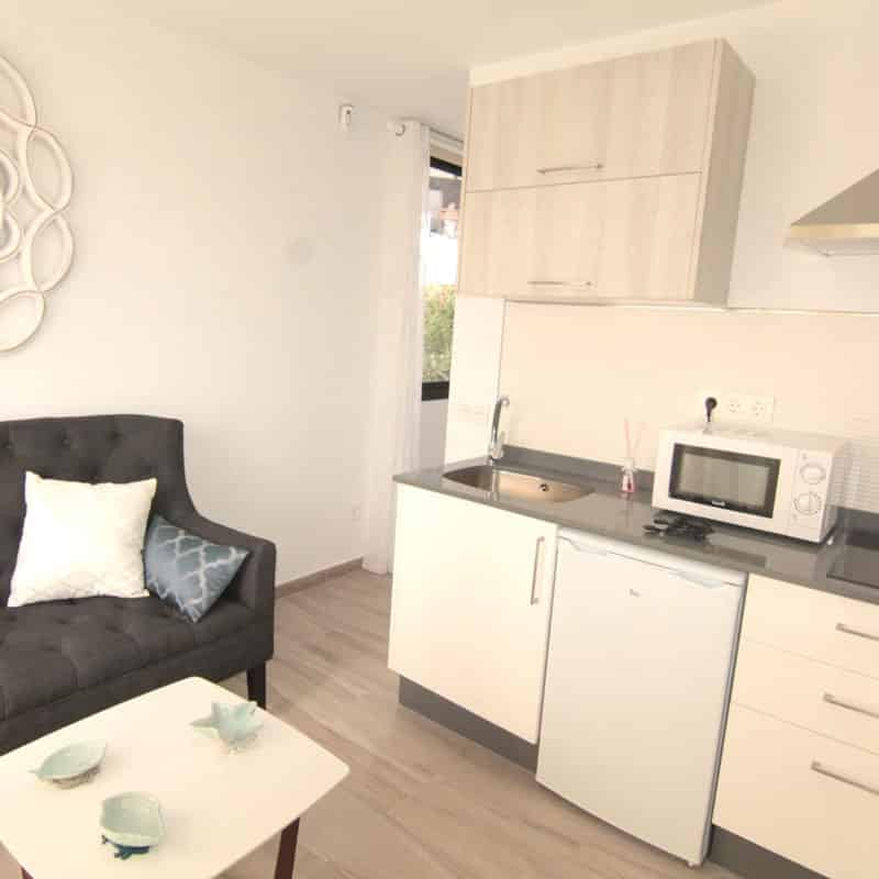 estudio los dises alojamiento en lanzarote salon cocina blanca con microondas y lavaplatos