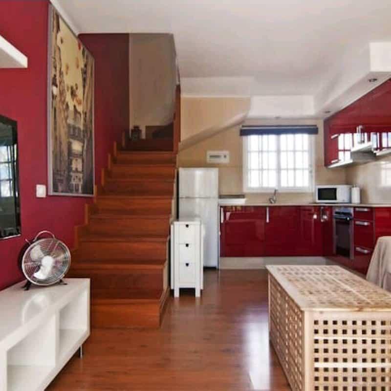 apartamentos duplex las marinas cocina roja con nevera horno microondas y una mesa blanca ventilador
