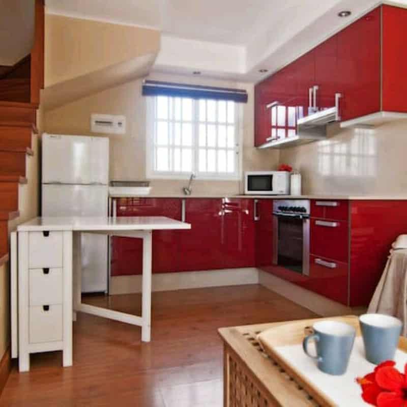 apartamentos duplex las marinas cocina roja con nevera horno microondas y una mesa blanca con vasos azules
