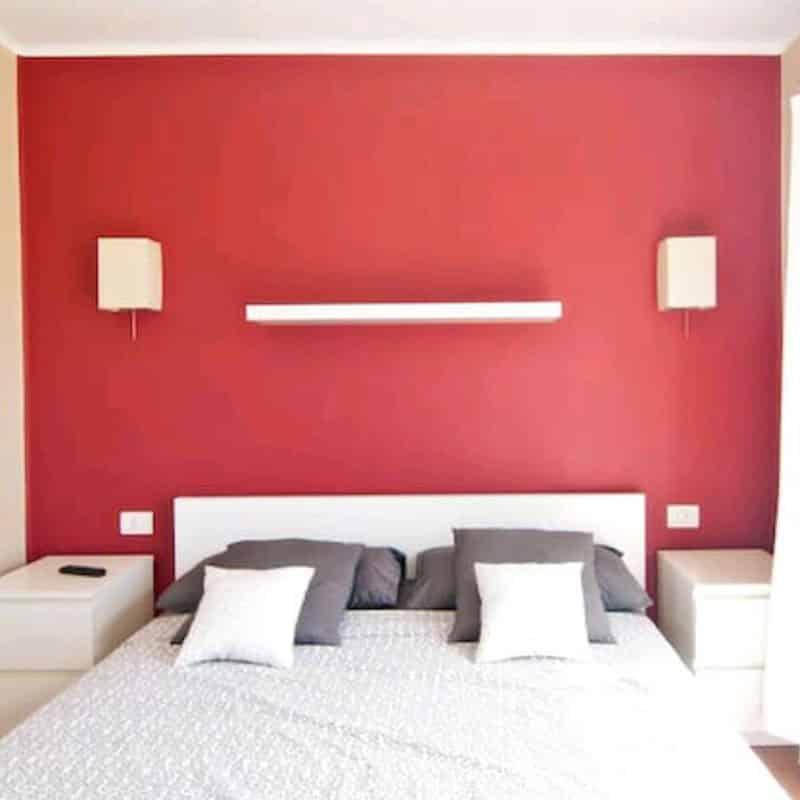 apartamentos duplex las marinas habitacion roja con cama blanca estanteria y mesitas de noche