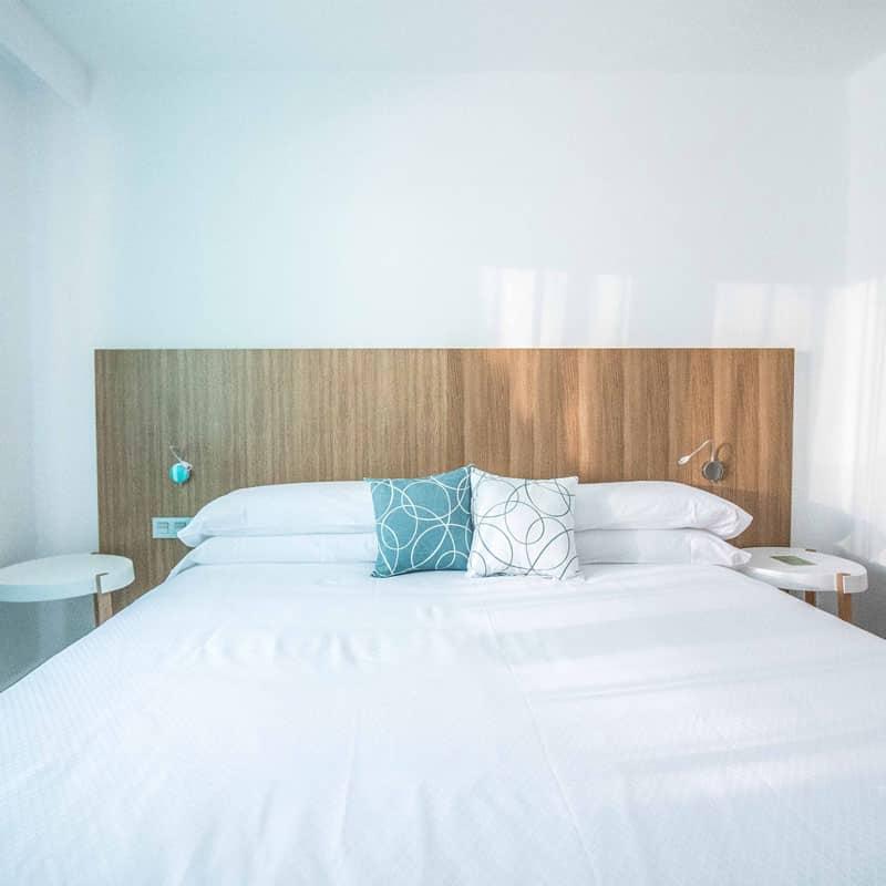mojo dive apartamentos guinate club moderna habitacion blanca con cabecero de madera y cojines azules