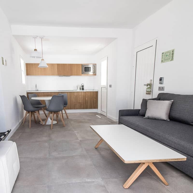 mojo dive apartamentos guinate club moderno salon cocina con sofas y sillas grises y mesas blancas