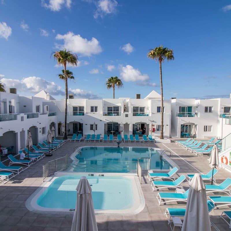 mojo dive apartamentos guinate club piscina y hamacas azules con palmeras y edificios blancos