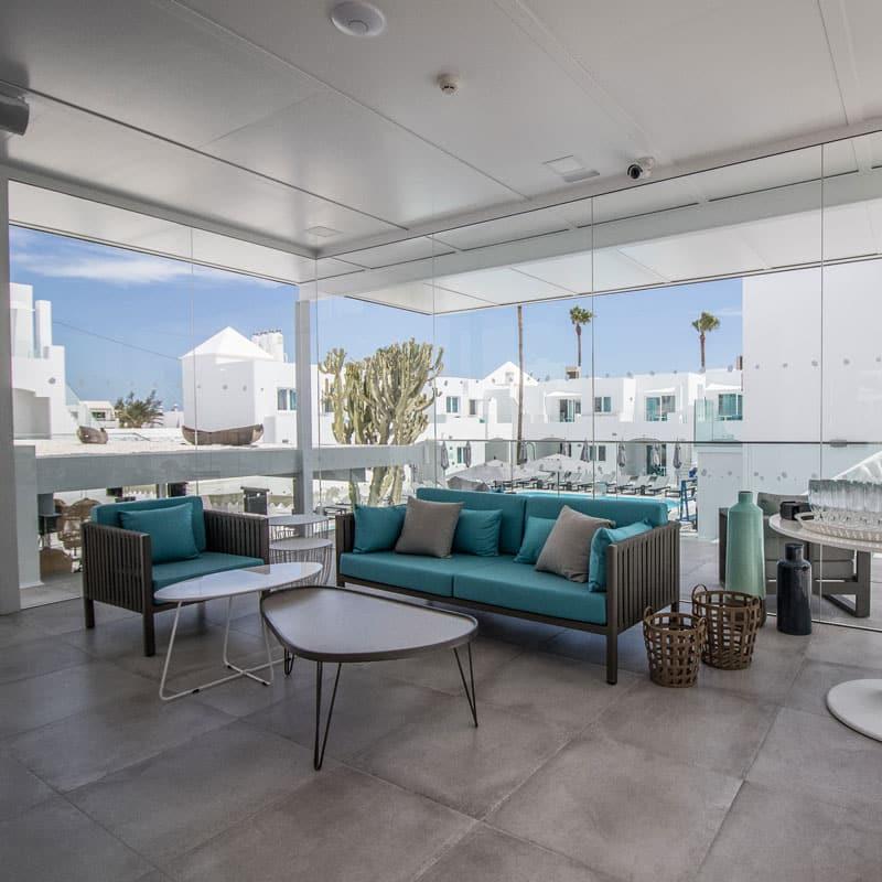 mojo dive apartamentos guinate club con casas blancas de fondo y sillones turquesa