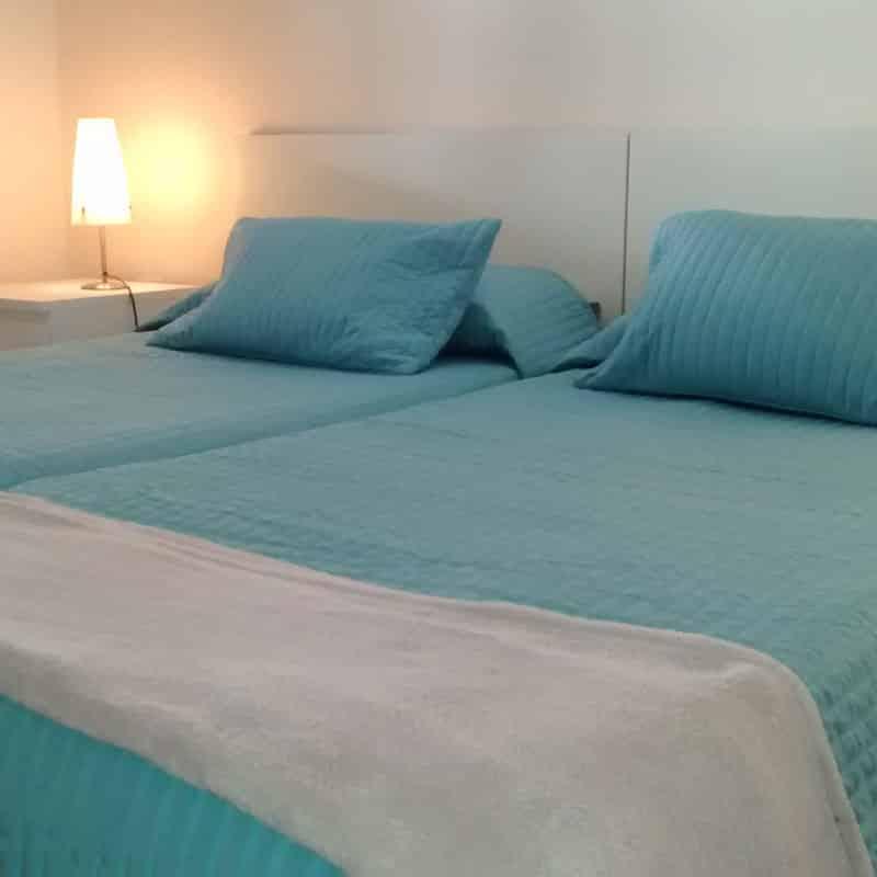 apartamentos la florida con dos camas individuales azules y una lampara