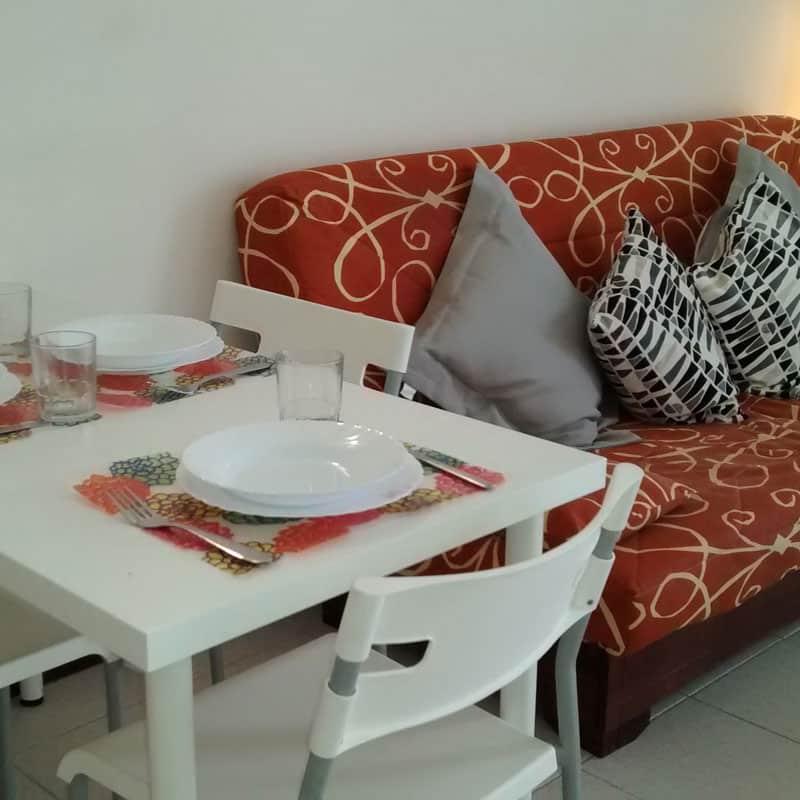 apartamentos la florida salon blanco con sofa rojo y cojines grises