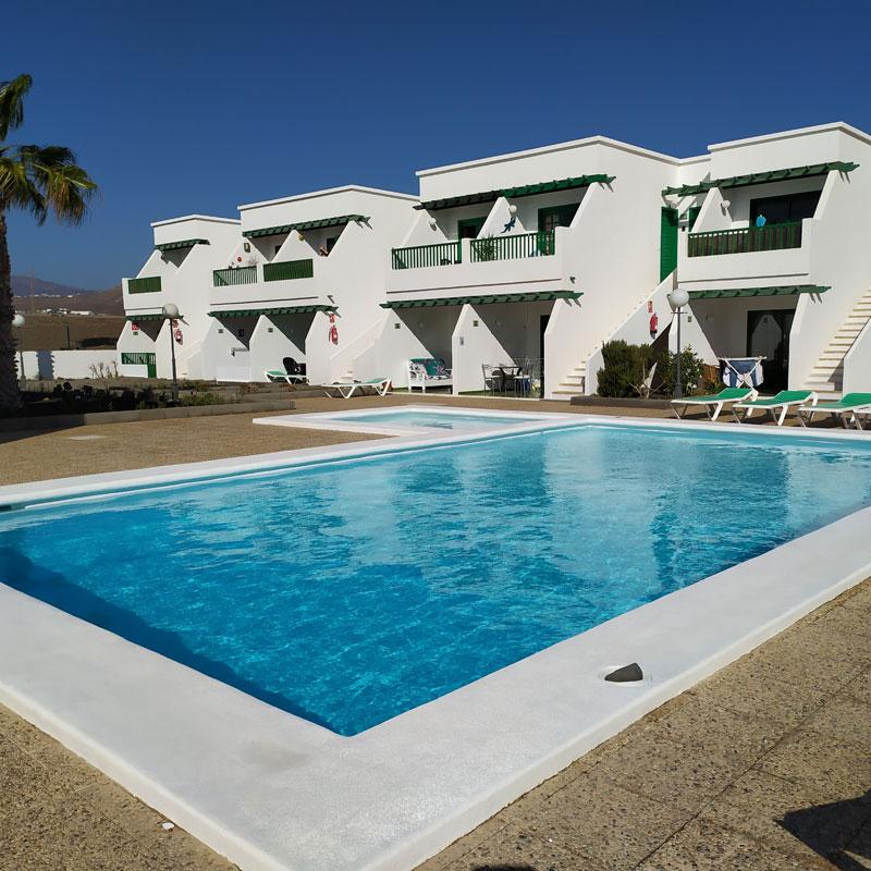 estudio rocas negras alojamiento en lanzarote con piscina y edificios blancos