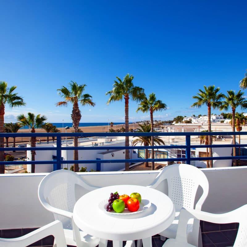 aparthotel costamar con vistas al mar con mesa y sillas blancas