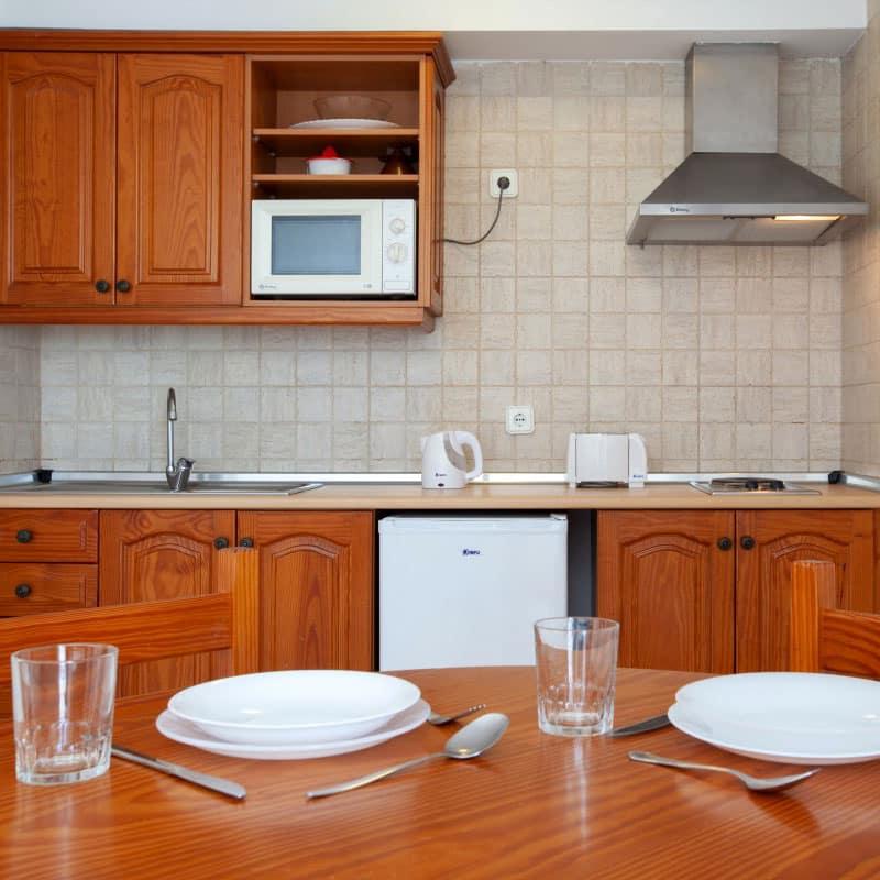 aparthotel costamar cocina de madera con hornillo microondas y lavaplatos
