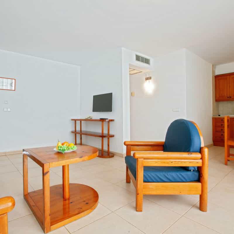 aparthotel costamar salon de madera con azul y paredes blancas con television moderna