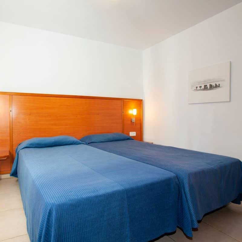 aparthotel costamar habitacion doble de madera con sabas azules y un cuadro en blanco y negro