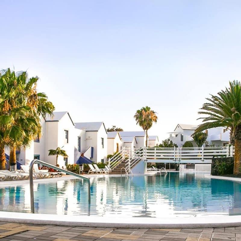 aparthotel marromar piscina con palmeras y casas blancas de fondo