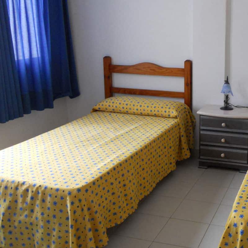 club pocillos con habitacin antigua con sabanas amarillas y cortinas azules