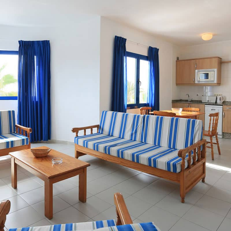 club pocillos con muebles de madera y television antigua con ventanas y cortinas azules