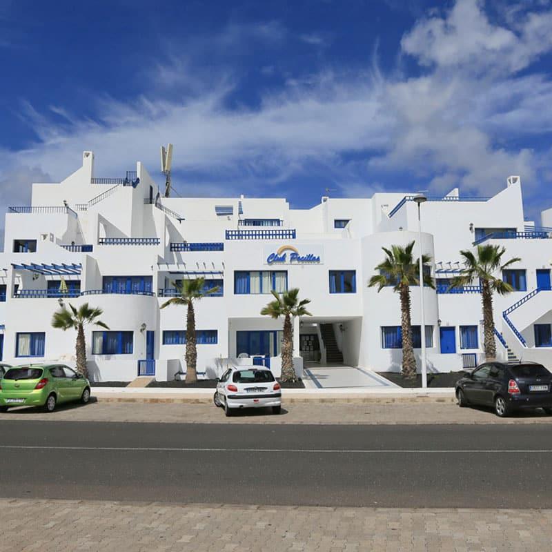 club pocillos edificios blancos con cielo azul y ventas y puertas azules