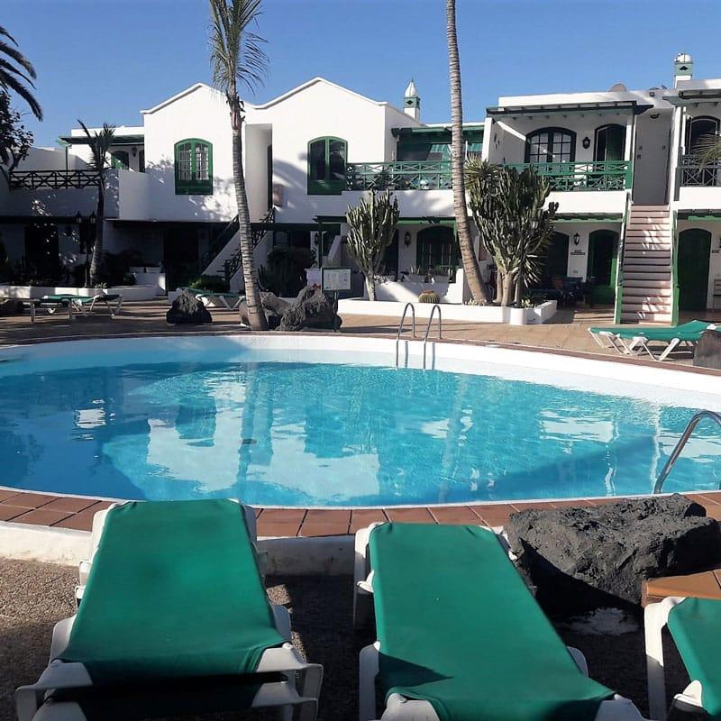 estudio rocas negras alojamiento en lanzarote piscina azul con casas blancas con ventanas y puertas verdes