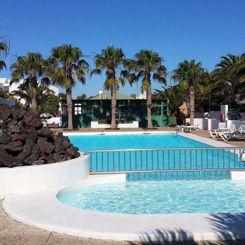 apartamentos duplex las marinas piscina azul para niños y palmeras